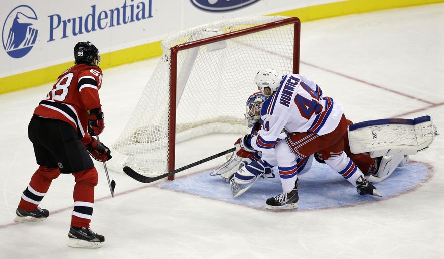 New Jersey Devils' Jaromir Jagr (68), of the Czech Republic, scores a goal as New York Rangers goalie Cam Talbot (33) and Matt Hunwick (44) look at the puck in the top corner of the net during the second period of an NHL hockey game Saturday, Oct. 4, 2014, in Newark, N.J. (AP Photo/Mel Evans)