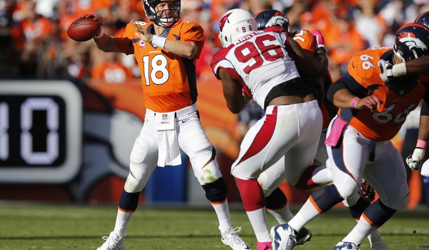 Denver Broncos quarterback Peyton Manning (18) throws as Arizona Cardinals defensive end Kareem Martin (96) pursues during the second half of an NFL football game, Sunday, Oct. 5, 2014, in Denver. (AP Photo/David Zalubowski)