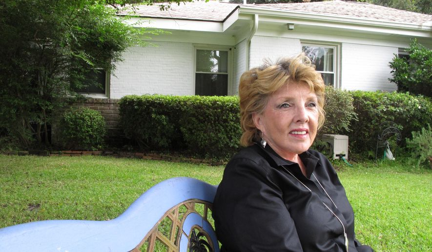 Pam Miller sits on a bench in front of her home in the Kensington Park neighborhood in Savannah, GA., on Friday, Sept. 26, 2014. After years of efforts by Miller and other Kensington Park residents, the 1950s suburb was recently added to the National Register of Historic Places, joining Savannah's more famous neighborhoods that pre-date the Civil War on the official list of America's historic treasures. (AP Photo/Russ Bynum)