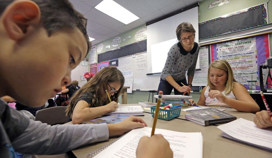 In this Thursday, Oct. 2, 2014, photo, teacher Joy Burke checks on the work of her fifth grade students at John Hay Elementary school in Seattle. (AP Photo/Elaine Thompson) ** FILE **