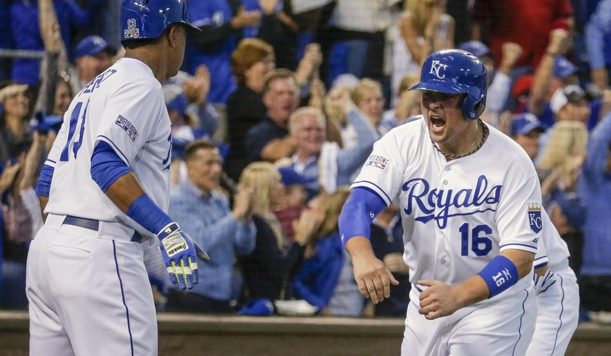 Kansas City Royals designated hitter Billy Butler (16)  celebrates with Kansas City Royals catcher Salvador Perez (13) after Butler scored on a 3-RBI double by Alex Gordon during the first inning of Game 3 of baseball's AL Division Series against the Los Angeles Angels in Kansas City, Mo., Sunday, Oct. 5, 2014. (AP Photo/Charlie Riedel)