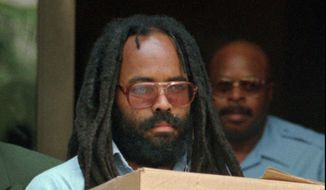 In this July 12, 1995, file photo, convicted police killer and death-row activist Mumia Abu-Jamal leaves Philadelphia's City Hall after a hearing. Mumia Abu-Jamal, a one-time death row inmate now serving a life sentence for the 1981 murder of a Philadelphia police officer spoke to students graduating from a Vermont college on Sunday, Oct. 5, 2014, encouraging them to strive to transform the world.(AP Photo/Chris Gardner, File)