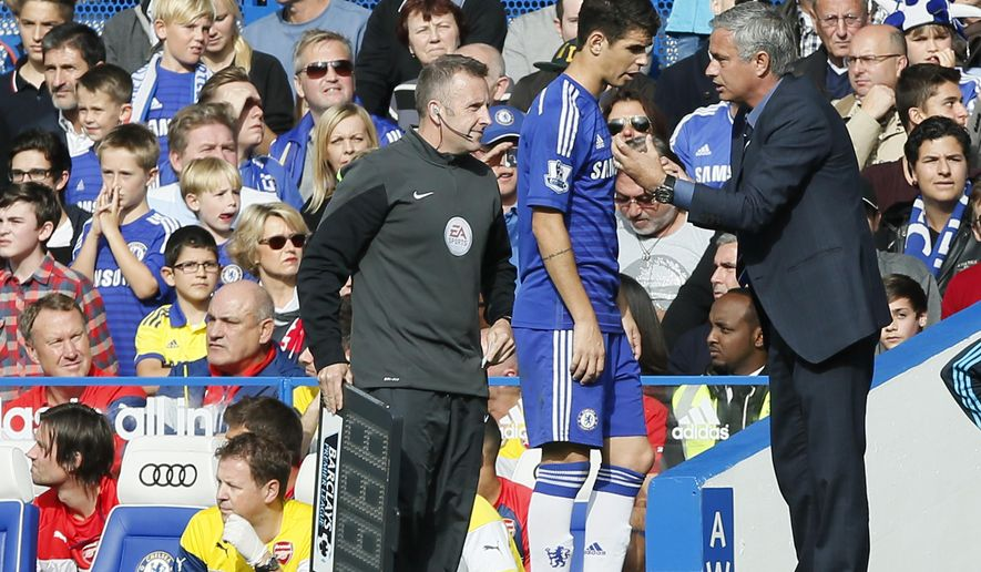 Chelsea manager Jose Mourinho, right, talks to his player Oscar on the sidelines during their English Premier League soccer match between Chelsea and Arsenal at Stamford Bridge stadium in London Sunday, Oct. 5, 2014. (AP Photo/Alastair Grant)