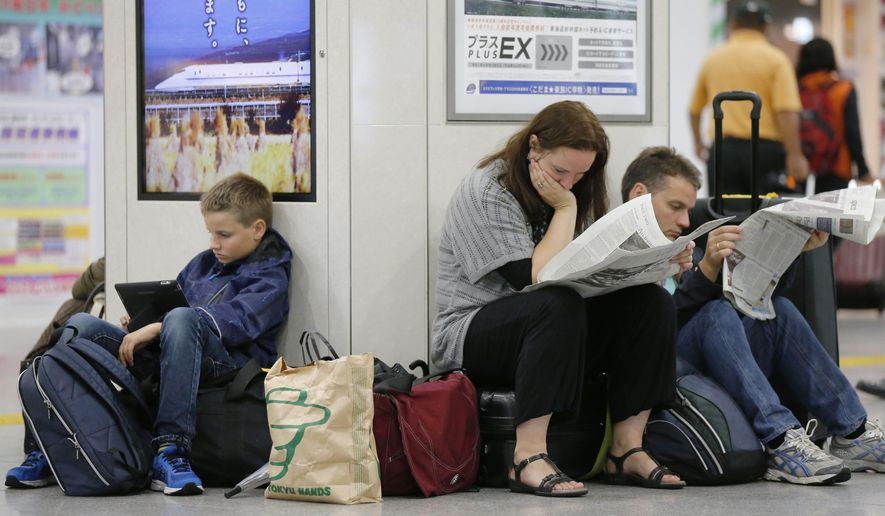 Tourists read newspapers while bullet train services are suspended because of a powerful typhoon, at Tokyo Station in Tokyo Monday, Oct. 6, 2014.  (AP Photo/Kyodo News) JAPAN OUT, MANDATORY CREDIT