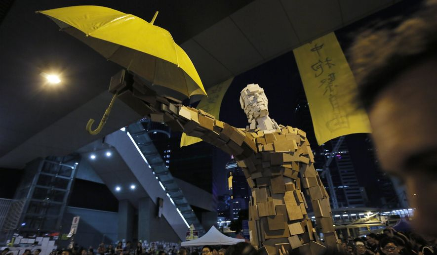 A statue holding a yellow umbrella set up by students stands outside government headquarters in Hong Kong, Sunday, Oct. 5, 2014. In an apparent concession to authorities warning pro-democracy protesters to clear Hong Kong's streets by the beginning of the work week, students occupying the area outside city government headquarters agreed Sunday to remove some barricades that have blocked the building's entrance during the weeklong demonstrations. But it was not immediately clear how significant the move was and how much it would defuse the standoff, with many protesters vowing to stay in the area.  (AP Photo/Vincent Yu)