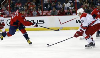 Washington Capitals right wing Alex Ovechkin (8), from Russia, has his shot deflected by Carolina Hurricanes defenseman John-Michael Liles (26) in the first period of a preseason NHL hockey game, Sunday, Oct. 5, 2014, in Washington. (AP Photo/Alex Brandon)