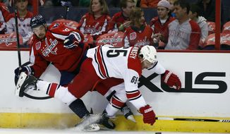 Washington Capitals forward Liam O'Brien (87) and Carolina Hurricanes defenseman Ron Hainsey (65) battle for the puck in the first period of a preseason NHL hockey game, Sunday, Oct. 5, 2014, in Washington. (AP Photo/Alex Brandon)