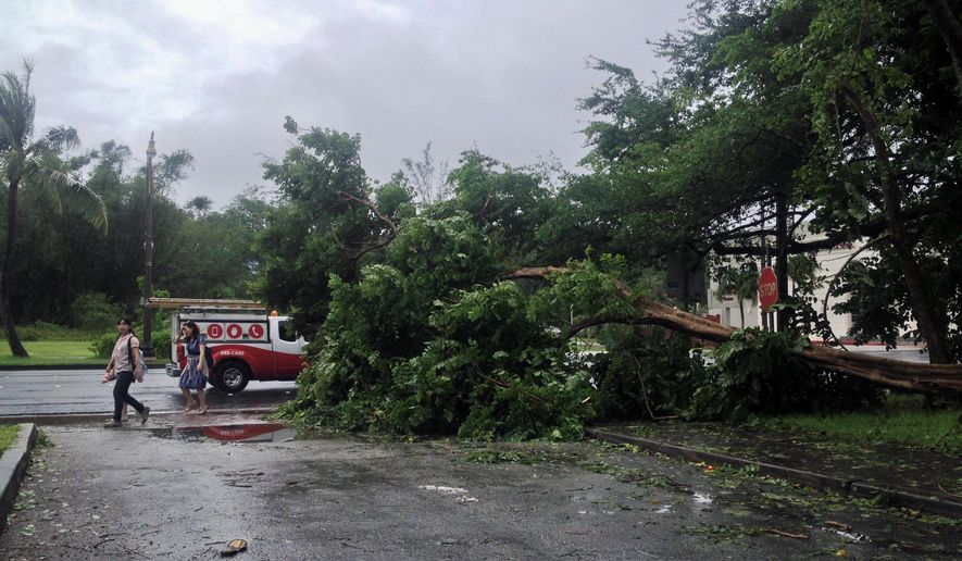 A fallen tree blocks a sidewalk in Tumon, Guam, Monday, Oct. 6, 2014. A typhoon whipped the Mariana Islands, including Guam, with high winds and heavy rain. As conditions improved, Guam officials shut down the island's storm center, the airport resumed full operations, and government agencies and many businesses began reopening. (AP Photo/Grace Garces Bordallo)