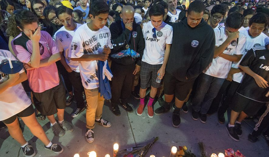 Attendees mourn during a candlelight vigil at Capistrano Valley High School on Sunday, Oct. 5, 2014, in Mission Viejo, Calif. Five students died in a single-vehicle car crash early Saturday. (AP Photo/The Orange County Register, Kyusung Gong) MAGS OUT; LOS ANGELES TIMES OUT