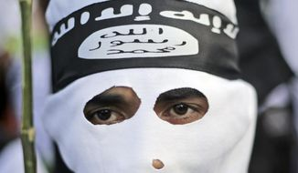 A Muslim man wears a headband showing the Islamic State group's symbol. A lax legislative approach in some European countries makes it hard to prosecute returning militants. (Associated Press/File)