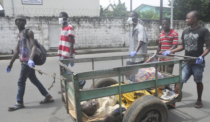 Volunteers push cart with a man suspected of having Ebola virus, to a health centre in central area Monrovia, Liberia, Sunday, Oct. 5, 2014.  (AP Photo/Abbas Dulleh)