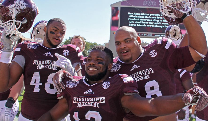 Mississippi State players including defensive lineman Ryan Brown (48), running back Josh Robinson (13) and defensive lineman Nick James (88) celebrate after their 48-31 win over No. 5 Texas A&M in an NCAA college football game in Starkville, Miss., Saturday, Oct. 4, 2014. (AP Photo/Jim Lytle)