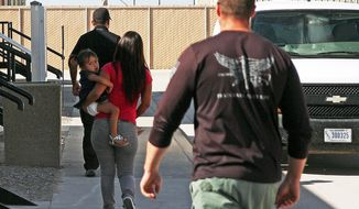 A woman and child are escorted to a van by detention facility guards inside the Artesia Family Residential Center, a federal detention facility for undocumented immigrant mothers and children, in Artesia, N.M. (Associated Press)