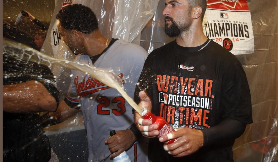 Baltimore Orioles' Nick Markakis, right, and Nelson Cruz celebrate after Baltimore defeated the Detroit Tigers, 2-1, in Game 3 of baseball's AL Division Series Sunday, Oct. 5, 2014, in Detroit. Baltimore won the series 3-0. (AP Photo/Paul Sancya)