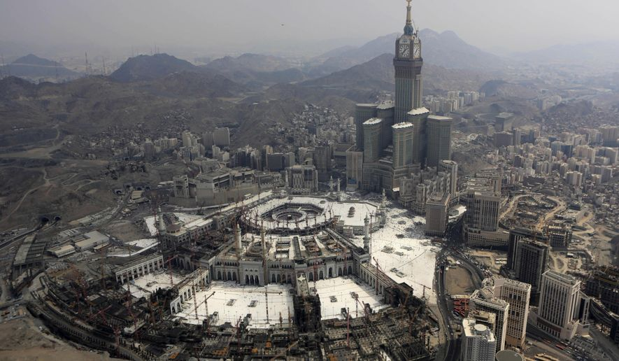 The Abraj Al-Bait Towers with the four-faced clocks stands over the holy Kabaa, as Muslims encircle it inside the Grand Mosque during the annual pilgrimage, known as the hajj, in the Muslim holy city of Mecca, Saudi Arabia, Sunday, Oct. 5, 2014. Muslims around the world celebrated the start of Islam's biggest holiday on Saturday as more than 2 million pilgrims took part in one of the final rites of the annual hajj pilgrimage in Saudi Arabia. (AP Photo/Khalid Mohammed)
