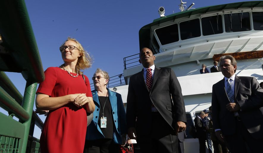 U.S. Department of Transportation Secretary Anthony Foxx, center, stands on the deck of a Washington state ferry with Lynn Peterson, left, Washington state Secretary of Transportation, and Lynne Griffith, second from left, assistant secretary for the Washington State Ferries Division, as they ride between Seattle and Bainbridge Island, Wash., Monday, Oct. 6, 2014. Foxx was in town at the invitation of U.S. Sen. Patty Murray, D-Wash., to learn more about Washington's ferry system and the need for both state and federal funding. (AP Photo/Ted S. Warren)