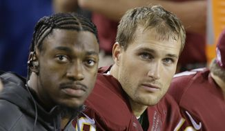 Washington Redskins quarterback Robert Griffin III and quarterback Kirk Cousins (8) watch the action from the bench during the first half of an NFL football game against the Seattle Seahawks in Landover, Md., Monday, Oct. 6, 2014. Griffin is still recovering from an injury. (AP Photo/Patrick Semansky)