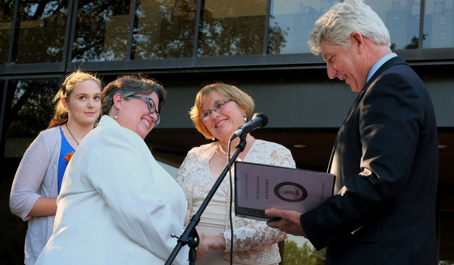 Virginia Attorney General Mark Herring, right, leads a renewal of vows for former plaintiffs Mary Townley, second from left, and her partner Carol Schall, second from right, outside the John Marshall Courts Building in Richmond, Va. Monday, Oct. 6, 2014. The Richmond area couple challenged Virginia's marriage ban. (AP Photo/Richmond Times-Dispatch, Bob Brown).