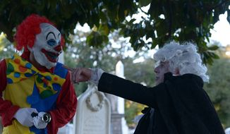 Paul Williams, president of Historic Congressional Cemetery in Southeast, right, points to were he wants his scary clown to hide before the start of the the annual Dead Man's Run, a 5K run through the cemetery and surrounding area, on Saturday, Oct. 4, 2014. ** FILE **