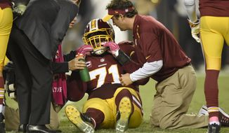 Trainers check Washington Redskins tackle Trent Williams (71) after an injury during the second half of an NFL football game against the Seattle Seahawks in Landover, Md., Monday, Oct. 6, 2014. (AP Photo/Nick Wass)