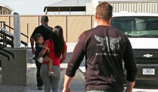 FILE- In this Sept. 10, 2014 file photo, a woman and child are escorted to a van by detention facility guards inside the Artesia Family Residential Center, a federal detention facility for undocumented immigrant mothers and children in Artesia, N.M, A surge of cases involving immigrants from Central America has backed up federal courts and U.S. Immigration and Customs Enforcement. The cases have been moved to Denver by judges in Arlington, Va. Officials say it makes more sense to hold the proceedings in the same time zone as the detention center. Hearings are being held by video from Artesia, N.M. starting on Monday, Sept. 29. (AP Photo/Juan Carlos Llorca, File)