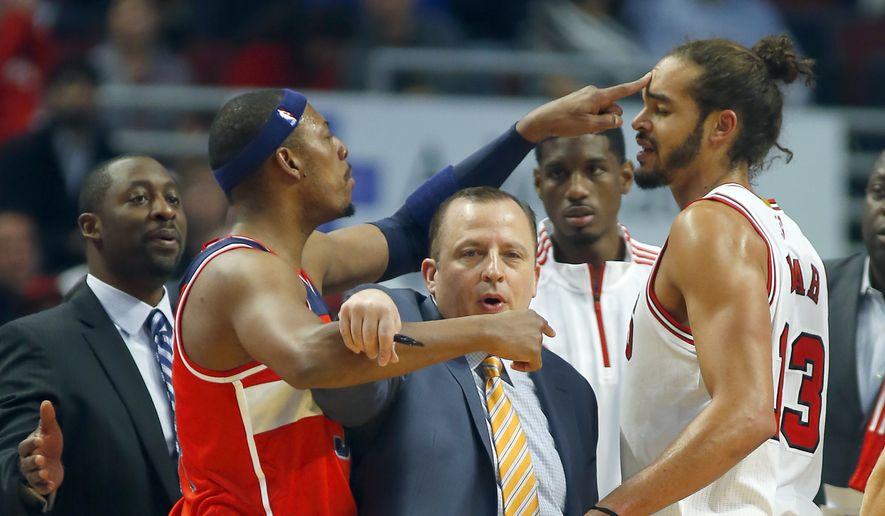 Washington Wizards forward Paul Pierce, left, pokes Chicago Bulls center Joakim Noah, rigth, in the head during a time-out as Bulls head coach Tom Thibodeau, center, gets between the two during the first half of a pre-season NBA basketball game in Chicago, on Monday Oct. 6, 2014. (AP Photo/Jeff Haynes)