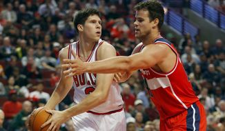 Chicago Bulls forward Doug McDermott, left, is guarded by Washington Wizards forward Kris Humphries, right, during the first half of a preseason NBA basketball game in Chicago, Monday Oct. 6, 2014. (AP Photo/Jeff Haynes)