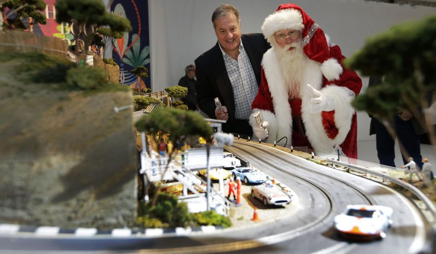 Brady Smith, as Santa Claus, right, and David Beattie check out the Slot Mods USA Ultimate Slot Car Raceway during the unveiling of the Neiman Marcus Christmas Book, Tuesday, Oct. 7, 2014, in Dallas. The cost of the 1:32 scale model race track is $300,000. (AP Photo/LM Otero)
