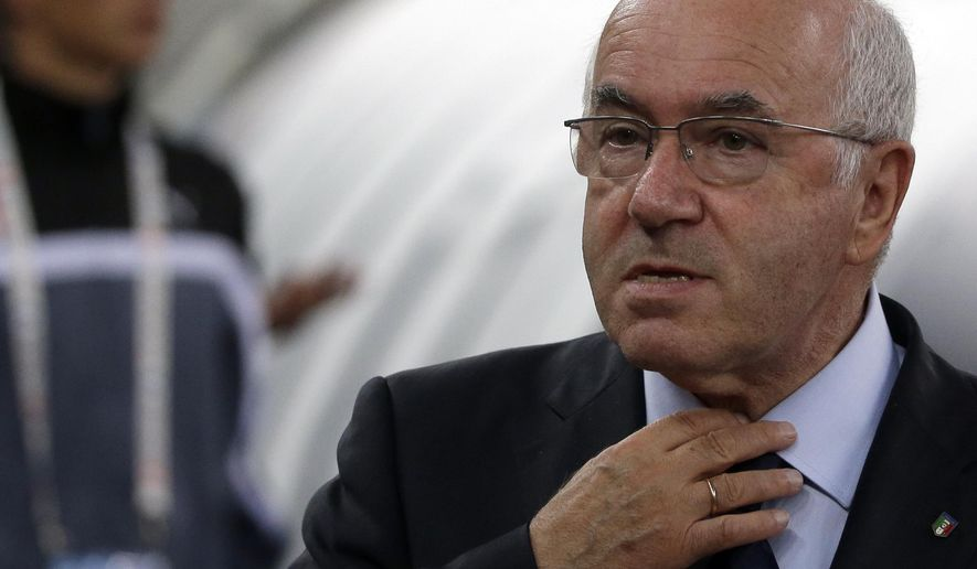 In this photo taken on Thursday, Sept. 4, 2014, Paolo Tavecchio adjusts his tie prior to a friendly soccer match between Italy and The Netherlands in Bari, Italy. UEFA has banned Italian soccer federation president Carlo Tavecchio for six months following a racist comment during his electoral campaign. Tavecchio, a long-standing executive in Italian football, was elected president in August despite causing a stir over a reference to bananas when discussing the presence of foreign players in Italy. (AP Photo/Gregorio Borgia)