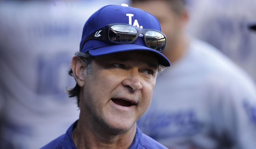 Los Angeles Dodgers manager Don Mattingly stands in the dugout during the second inning of Game 4 of baseball's NL Division Series against the St. Louis Cardinals, Tuesday, Oct. 7, 2014, in St. Louis. (AP Photo/Charles Rex Arbogast)