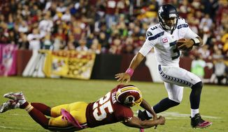 Seattle Seahawks quarterback Russell Wilson (3) breaks a tackle by Washington Redskins free safety Ryan Clark (25) during the second half of an NFL football game in Landover, Md., Monday, Oct. 6, 2014. (AP Photo/Alex Brandon)
