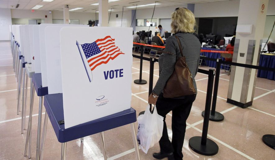 A woman walks past voting booths at the Cuyahoga County Board of Elections in Cleveland, Ohio, on Tuesday, Oct. 7, 2014, in this file photo. (AP Photo/Mark Duncan) **FILE**