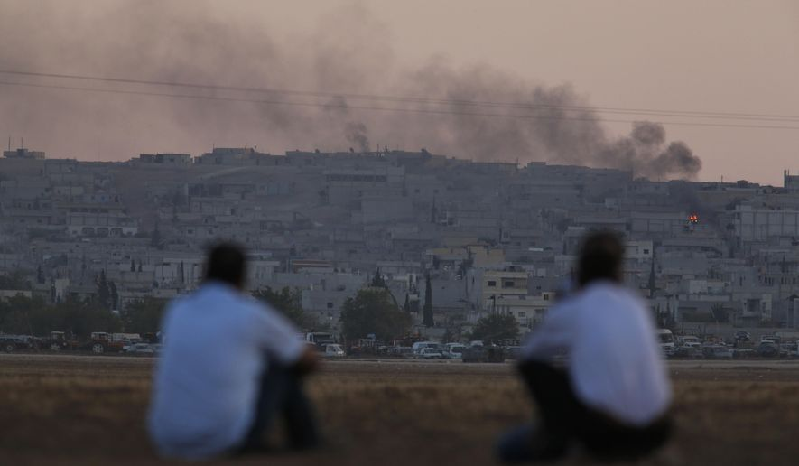 In this Oct. 7, 2014, file photo, Turkish Kurds sit on the outskirts of Suruc, on the Turkey-Syria border, as they watch smoke rising from a fire following an airstrike in Kobani, Syria, where the fighting between militants of the Islamic State group and Kurdish forces intensified. (AP Photo/Lefteris Pitarakis)