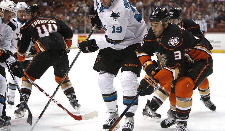 San Jose Sharks center Joe Thornton (19) works for the puck against Anaheim Ducks defenseman Clayton Stoner (3) during the first period of a preseason NHL hockey game in Anaheim, Calif., on Saturday, Oct. 4, 2014. (AP Photo/Christine Cotter)