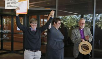 Nicole Pries, left, and Lindsey Oliver, center, hold up their marriage license as Rev. Robin Gorsline, right, applauds as they celebrate being one of the first same-sex couples in Virginia to be married outside a Richmond Court building in Richmond, Va., Monday, Oct. 6, 2014. The couple were the first in the Richmond area to be married after the US Supreme Court refused to overturn same-sex marriage prohibitions. (AP Photo/Steve Helber)