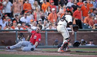 Washington Nationals Bryce Harper, right, scores past catcher Buster Posey on a throwing error by San Francisco Giants pitcher Madison Bumgarner in the seventh inning during Game 3 of baseball's NL Division Series in San Francisco, Monday, Oct. 6, 2014. (AP Photo/Marcio Jose Sanchez)