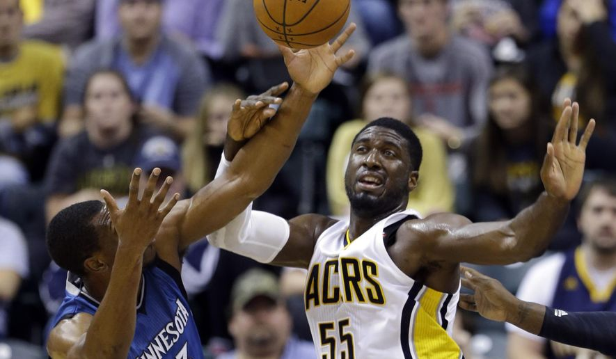 Minnesota Timberwolves forward Thaddeus Young, left, knocks the ball way from Indiana Pacers center Roy Hibbert during the first half of a preseason NBA basketball game in Indianapolis, Tuesday, Oct. 7, 2014. (AP Photo/Michael Conroy)