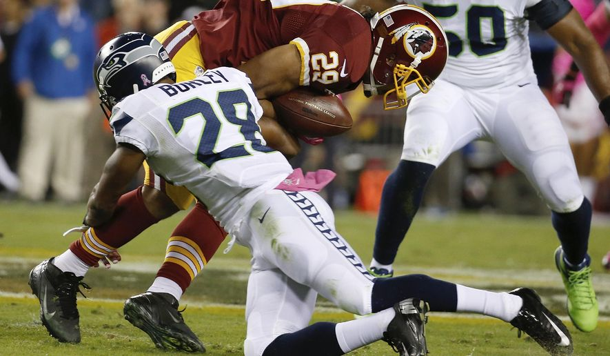 Washington Redskins running back Roy Helu (29) is stopped by Seattle Seahawks defensive back Marcus Burley (28) during the first half of an NFL football game in Landover, Md., Monday, Oct. 6, 2014. (AP Photo/Alex Brandon)