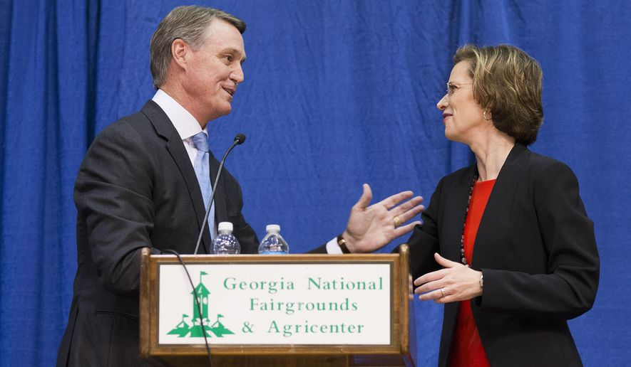 Georgia Democratic candidate for U.S. Senate Michelle Nunn, right, shakes hands with Republican candidate David Perdue following a debate, Tuesday, Oct. 7, 2014, in Perry, Ga. (AP Photo/David Goldman)