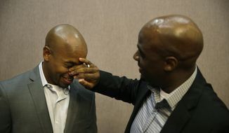 Nevada state Senator Kelvin Atkinson rubs tears from the eyes of Sherwood Howard during a rally to celebrate an appeals court ruling that overturned Nevada's gay marriage ban Tuesday, Oct. 7, 2014, in Las Vegas. Atkinson proposed to Howard when he had heard about the ruling Tuesday. (AP Photo/John Locher)