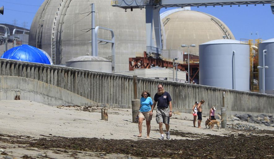 This June 30, 2011, file photo shows beach-goers walking on the sand near the San Onofre nuclear power plant in San Clemente, Calif. (AP Photo/Lenny Ignelzi, File)