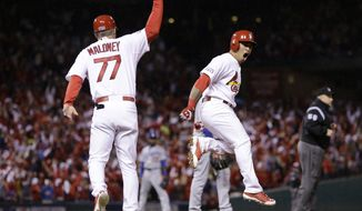St. Louis Cardinals' Kolten Wong, right,  reacts with first base coach Chris Maloney after hitting a two-run home run during the seventh inning of Game 3 of baseball's NL Division Series against the Los Angeles Dodgers, Monday, Oct. 6, 2014, in St. Louis. (AP Photo/Jeff Roberson)