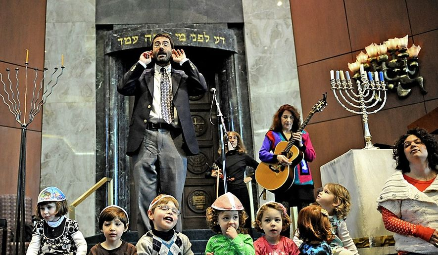 Rabbi Gil Steinlauf leads a group of children in song Friday during a celebration of the first night of Hanukkah at Adas Israel Congregation in Washington, D.C., in 2010. The rabbi has now come out as gay. (Joseph Silverman/The Washington Times)