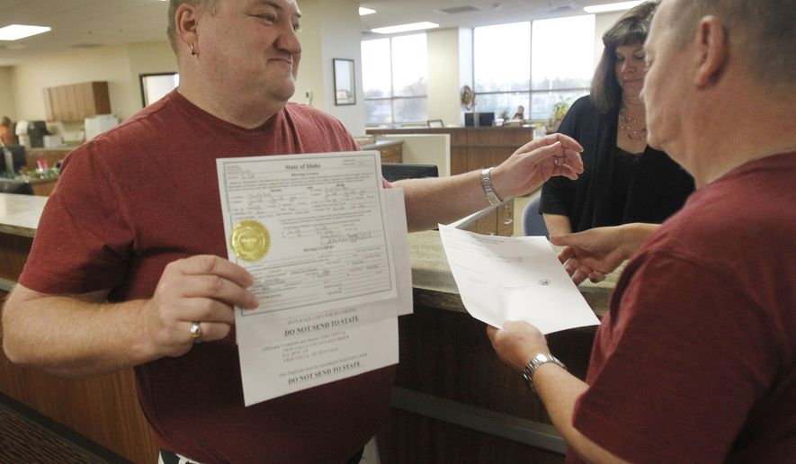 Don Moline holds up their marriage license as he embraces his partner Clint Newlan Wednesday morning, Oct. 8, 2014, at Twin Falls County West in Twin Falls, Idaho.  U.S. Supreme Court Justice Anthony Kennedy has temporarily blocked an appeals court ruling that declared gay marriage legal in the states of Idaho and Nevada. The order came minutes after Idaho on Wednesday filed an emergency request for an immediate stay. (AP Photo/The Times-News, Drew Nash) MANDATORY CREDIT