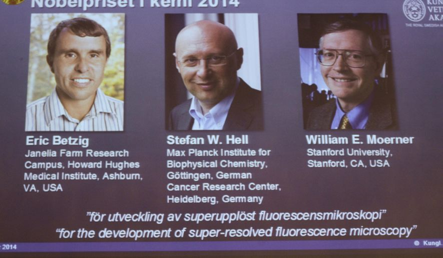 Images of the three winners of the 2014 Nobel Prize for Chemistry Americans Eric Betzig, left,  and William Moerner, right, and German scientist Stefan Hell, are projected on a screen at the Royal Swedish Academy of Sciences in Stockholm on Wednesday Oct. 8 2014 .  (AP Photo/Bertil Ericson)  SWEDEN OUT