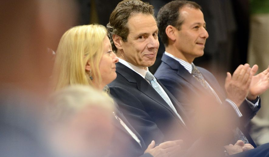 New York Gov. Andrew Cuomo receives applause alongside Heather Briccetti of the New York State Business Council and council member David Golub, right, of Price Chopper, after speaking at the Plug Power Inc. plant in Latham, N.Y., Wednesday, Oct. 8, 2014. A reelection endorsement was announced by the New York State Business Council during Cuomo's visit to the fuel cell company. (AP Photo/The Daily Gazette, Patrick Dodson)  TROY, SCHENECTADY; SARATOGA SPRINGS; ALBANY AND AMSTERDAM OUT
