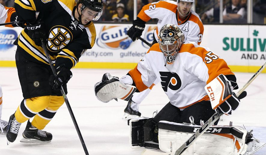 Boston Bruins right wing Reilly Smith (18) shoots but misses as Philadelphia Flyers goalie Steve Mason (35) protects the net in the second period of an NHL hockey game in Boston, Wednesday, Oct. 8, 2014. (AP Photo/Elise Amendola)