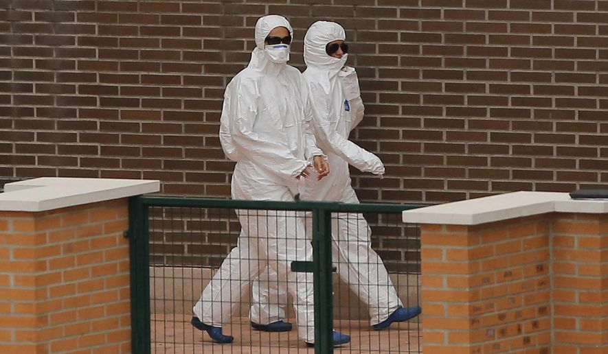 Medical staff wearing protective clothing arrives at the apartment building of the Spanish nurse infected with Ebola in Madrid, Spain, Wednesday, Oct. 8, 2014. Officials said a nurse and a nursing assistant have been placed under observation for Ebola in a Madrid hospital where a colleague became infected after working with two Spanish missionary priests who contracted the disease in West Africa and later died at the center. (AP Photo/Andres Kudacki)