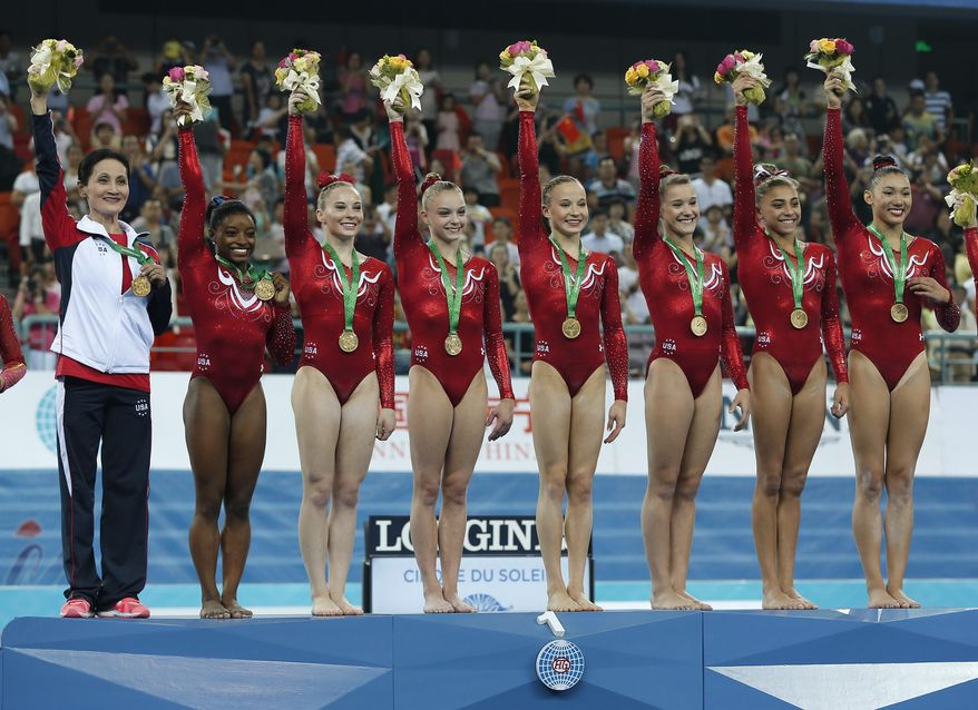 Gold medalist gymnasts of the United States raise flowers to celebrate on the podium after the awards ceremony of the women's team final of the Artistic Gymnastics World Championship at the Guangxi Gymnasium in Nanning, capital of southwest China's Guangxi Zhuang Autonomous Region Wednesday, Oct. 8, 2014. (AP Photo/Andy Wong)