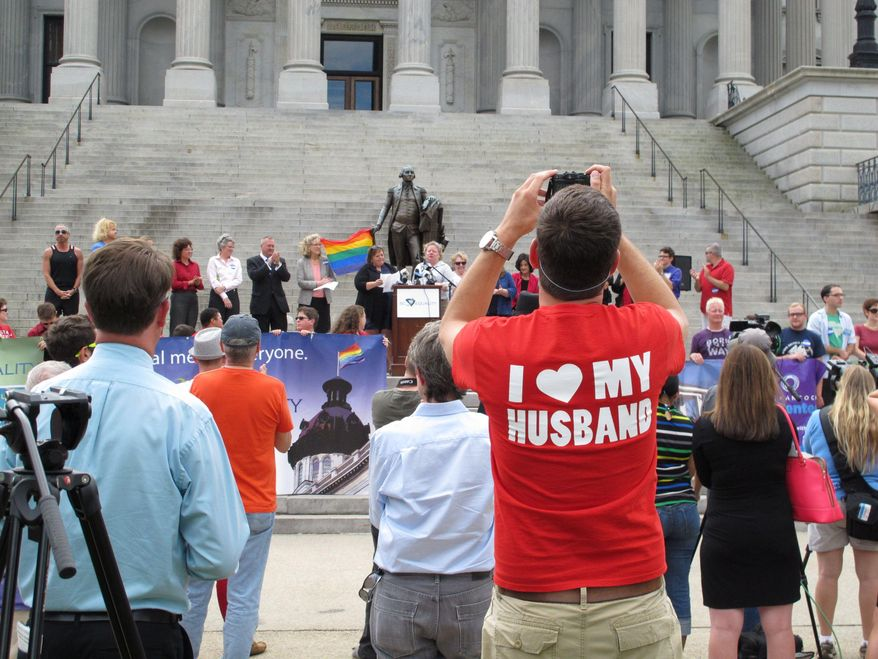Trevor Donovan takes pictures at a Statehouse rally on Wednesday, Oct. 8, 2014, in Columbia, S.C. Supporters of gay marriage held a rally at the capitol the same day a Charleston County Probate judge approved an application for a same-sex marriage license. (AP Photo/Jeffrey Collins)